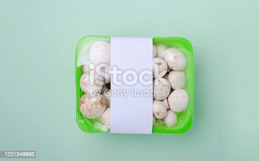 Closeup of fresh white edible mushrooms in the green box, blank white tag for price