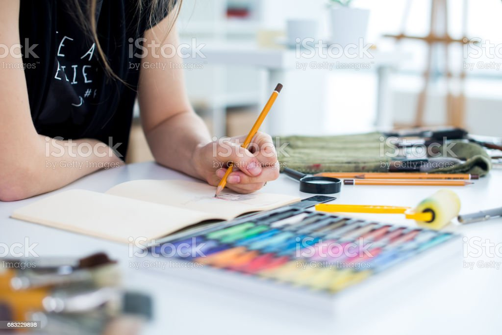 Close-up angle view of a female painter drawing draft at sketchbook using pencil. Artist sketching in art studio with crayons set. 免版稅 stock photo