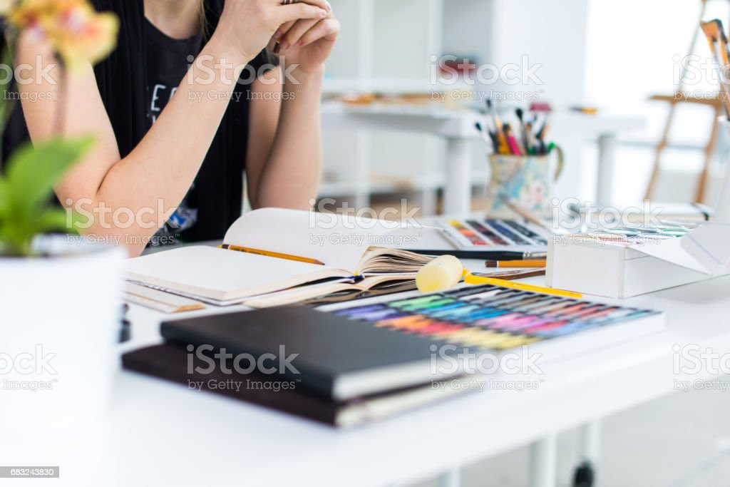 Close-up angle view of a female painter drawing draft at sketchbook using pencil. Artist sketching in art studio with crayons set. foto de stock royalty-free