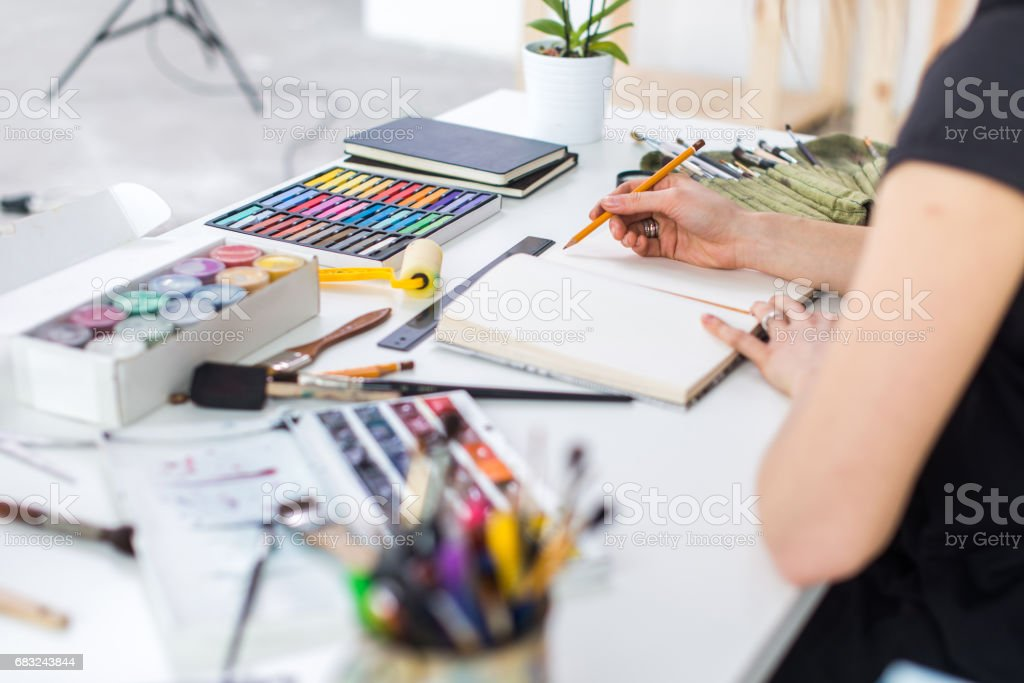 Close-up angle view of a female painter drawing draft at sketchbook using pencil. Artist sketching in art studio with crayons set. royalty-free 스톡 사진