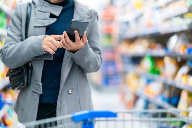 Nahaufnahme asiatische weibliche Hand halten Smartphone Überprüfen Preis vergleichen im Supermarkt mit Trolley Shopping Kart mit Reihe von Produkten – Foto