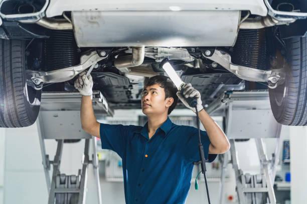 Closeup Asian mechanic hand repairing under the car in maintainance service center