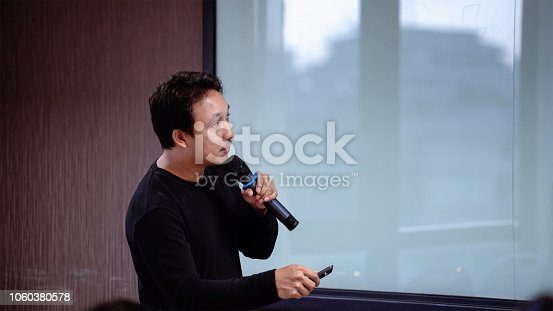 1158085965 istock photo Closeup Asian Speaker or lecture with casual suit on the stage in front of the room presenting with the screen in the conference hall or seminar meeting room, business and education concept 1060380578