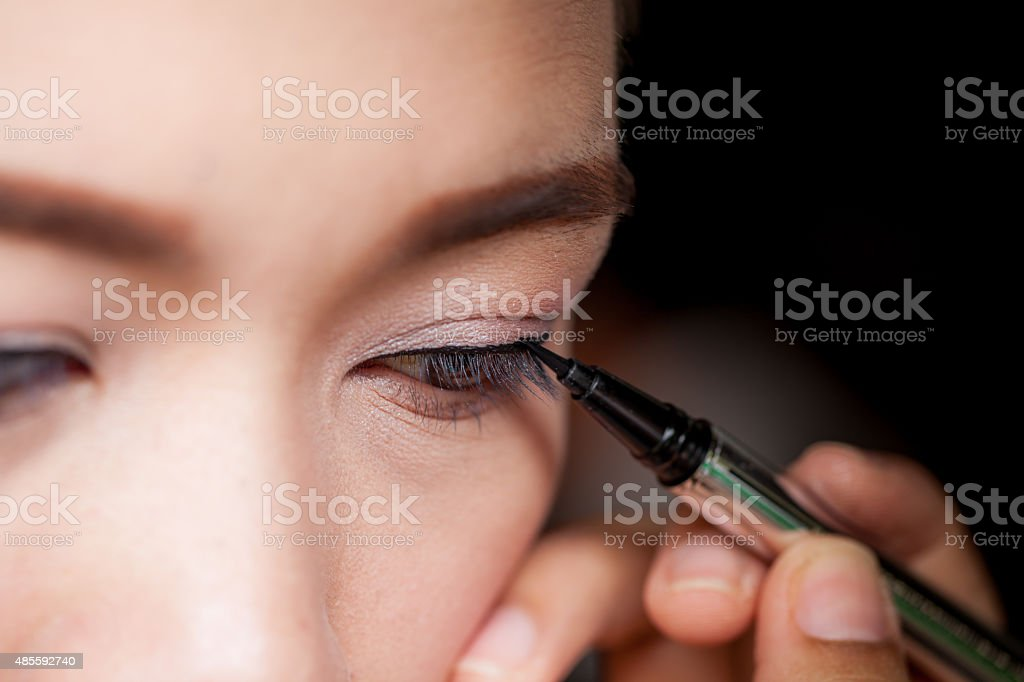 Closeup asian woman applying eyeliner on eye stock photo