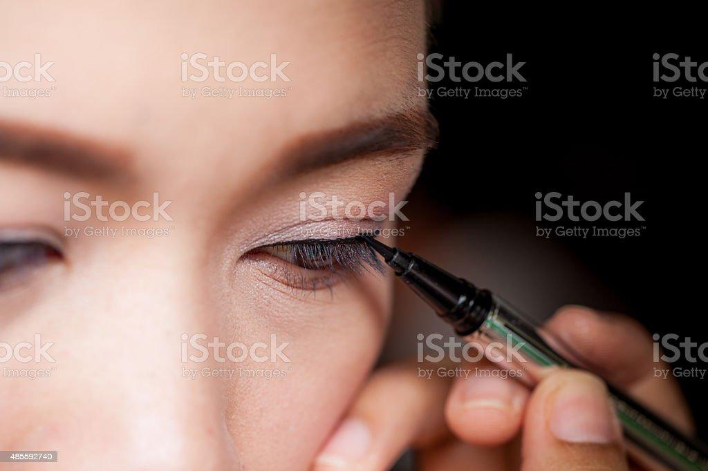 Closeup asian woman applying eyeliner on eye stock photo