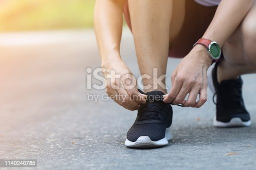 Closeup Asian woman tying her shoes while running on road in the park on morning, healthy concept