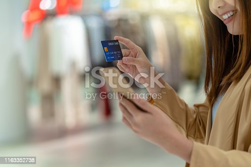 508915178istockphoto Closeup Asian woman using credit card with mobile for online shopping in department store over the clothes shop store background, technology money wallet and online payment concept, credit card mockup 1163352738
