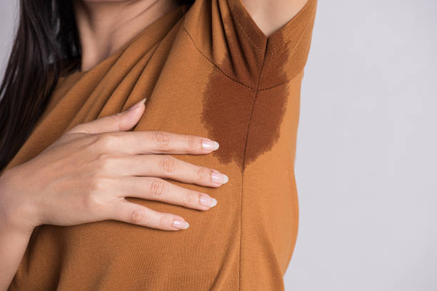 Close-up asian woman with hyperhidrosis sweating. Young asia woman with sweat stain on her clothes against grey background. Healthcare concept. Close-up asian woman with hyperhidrosis sweating. Young asia woman with sweat stain on her clothes against grey background. Healthcare concept. wet clothing women t shirt stock pictures, royalty-free photos & images