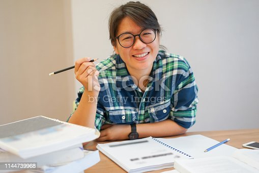 istock closeup asian young student woman smiling after finished reading book or research information at library , lifestyle education concept 1144739968