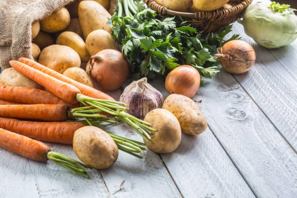 close-up sortiment an frischem gemüse. kartoffeln zwiebel karotte sellerie kohlrabi und knoblauch auf holz. - knoblauchkartoffeln stock-fotos und bilder