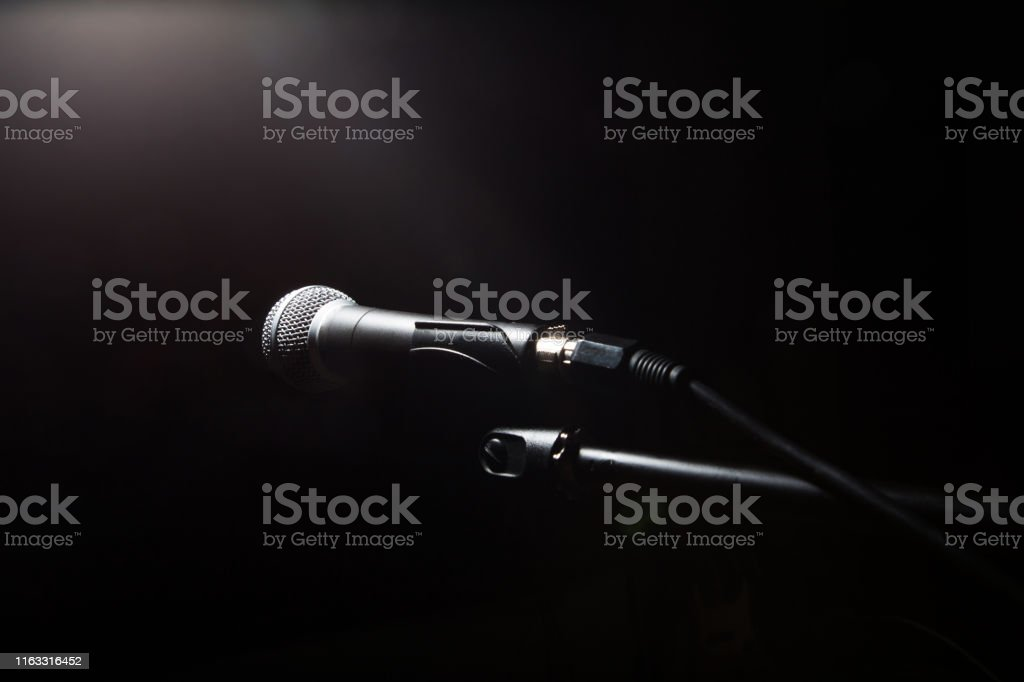 Close-up audio microphone on stand in black dark background . Music...