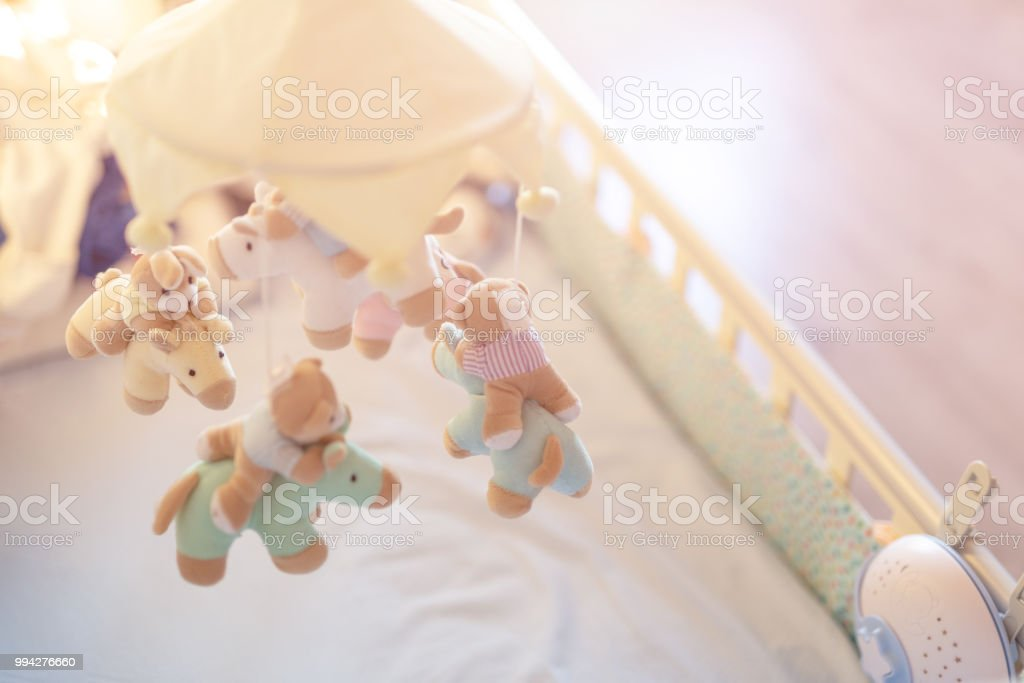 Close-up baby crib with musical animal mobile at nursery room. Hanged developing toy with plush fluffy animals. Happy parenting and childhood, expectation delivery of a child concept stock photo
