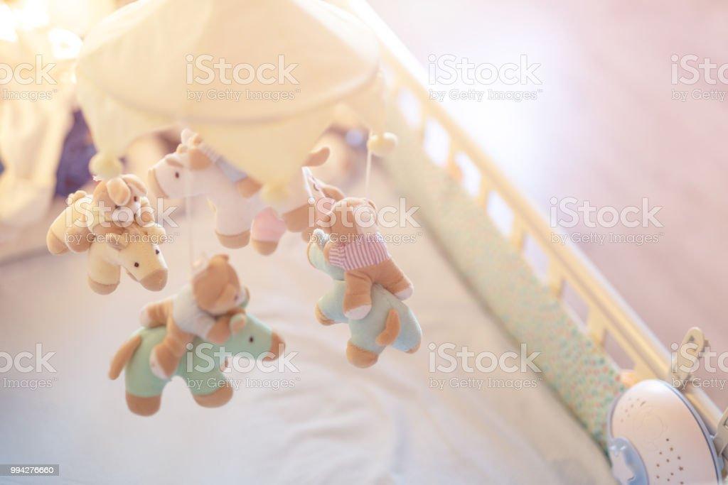 Berço de bebê de close-up com animal musical móvel na sala de berçário. Enforcado em desenvolvimento brinquedo com bichos de pelúcia fofos. Pais felizes e infância, entrega de expectativa de um conceito de criança - foto de acervo