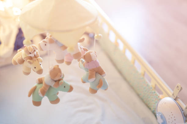Close-up baby crib with musical animal mobile at nursery room. Hanged developing toy with plush fluffy animals. Happy parenting and childhood, expectation delivery of a child concept Close-up baby crib with musical animal mobile at nursery room. Hanged developing toy with plush fluffy animals. Happy parenting and childhood, expectation delivery of a child concept. crib stock pictures, royalty-free photos & images