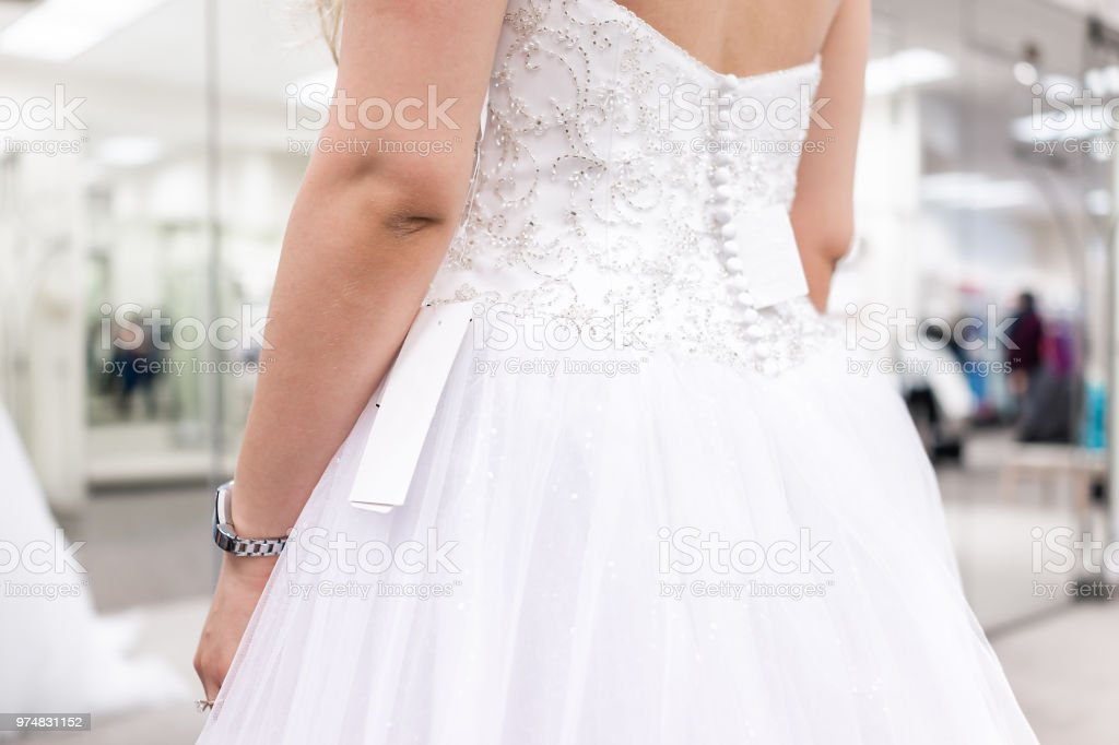 Closeup Back Of Young Woman Trying On White Button Wedding Dress