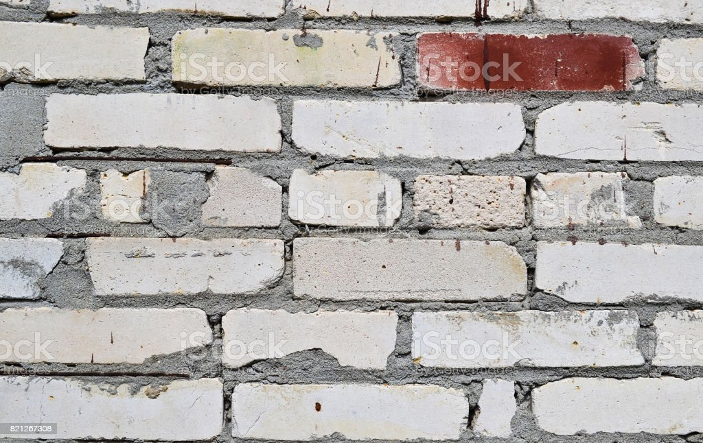 Close-up background of silicate brick wall. White or gray. One brick in red paint stock photo