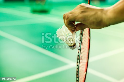 istock Closeup Badminton player hand holding the shuttle cock together with the racket, ready to serve position on the play green court with copy space 917259772