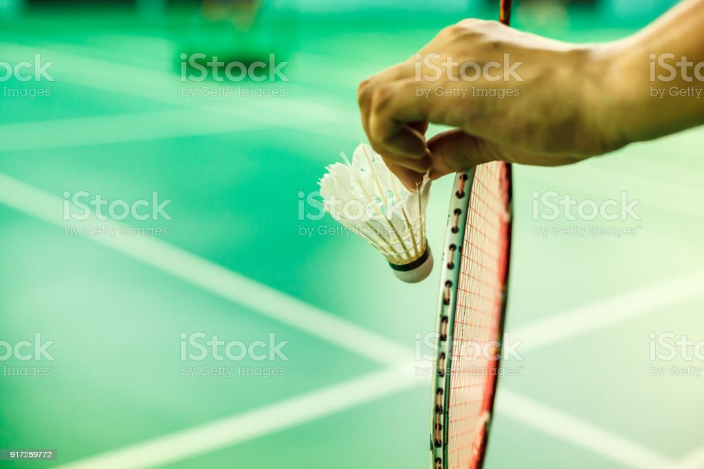Closeup Badminton player hand holding the shuttle cock together with the racket, ready to serve position on the play green court with copy space – zdjęcie
