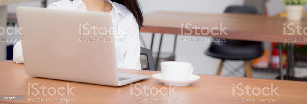 Closeup banner website asian young woman working online on laptop sitting  at coffee shop, professional