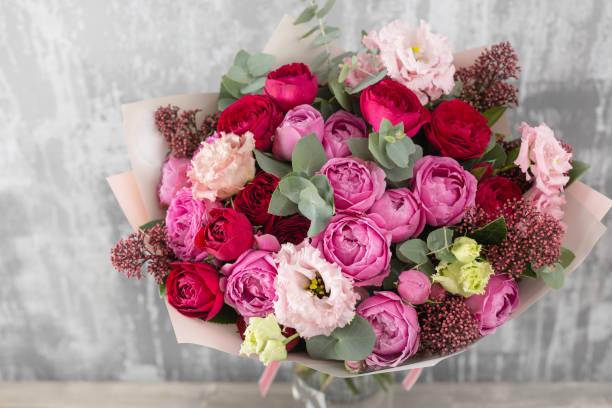 gros plan beau bouquet. fleurs de printemps sur fond gris. magasin de fleurs. table en bois - bouquet de fleurs photos et images de collection