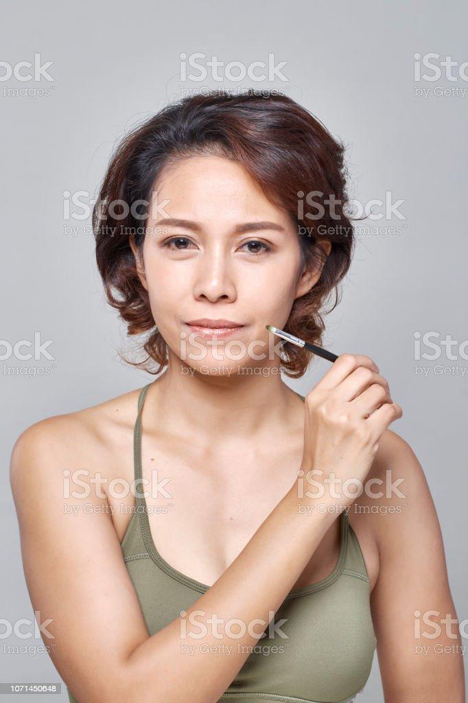 Closeup beautiful woman with eyebrow brush tool on gray стоковое фото