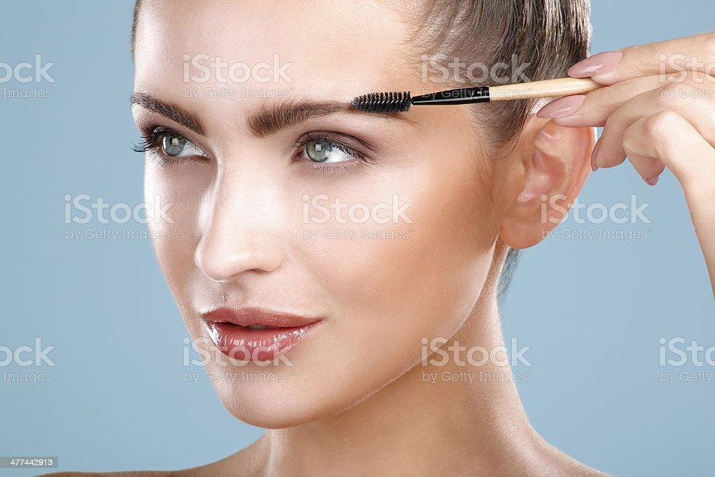Closeup beautiful woman with eyebrow brush tool stock photo