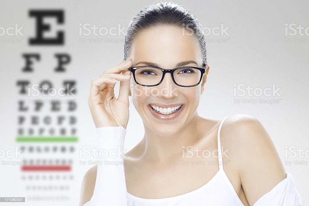 Close-up, beauty headshot of a beautiful smiling woman holding eyeglasses royalty-free stock photo