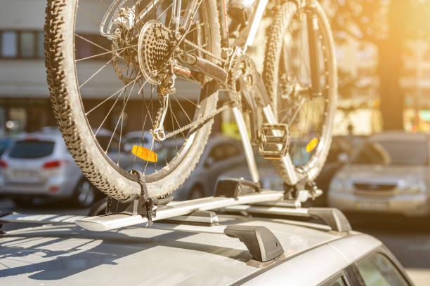close-up fahrrad auf auto dachträger reling im freien parken. fahrzeug mit montierten fahrrad auf dem dach. aktiv sport-touristische reise-konzept - fahrradträger stock-fotos und bilder