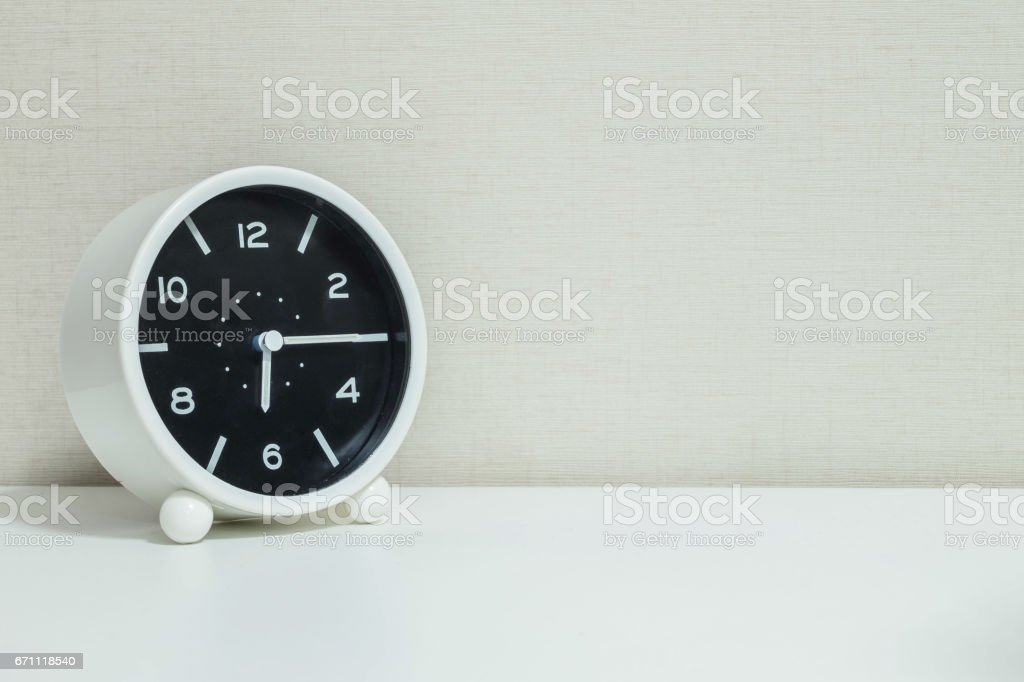 Closeup black and white alarm clock for decorate show a quarter past six or 6:15 a.m.on white wood desk and cream wallpaper textured background with copy space stock photo