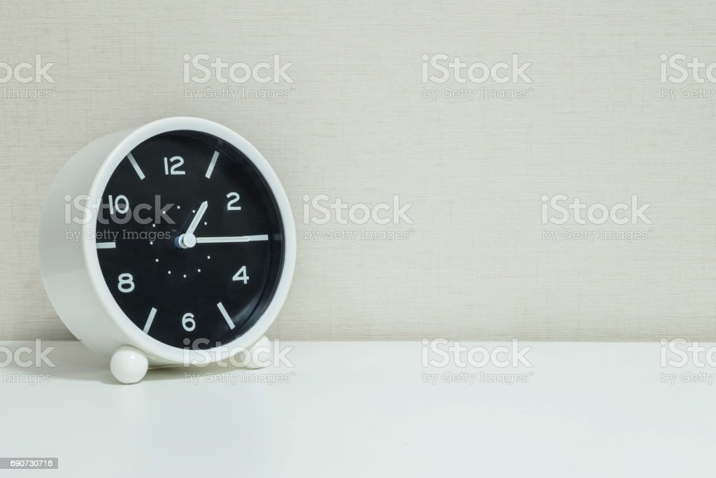 Closeup black and white alarm clock for decorate show a quarter past one or 1:15 p.m.on white wood desk and cream wallpaper textured background with copy space stock photo