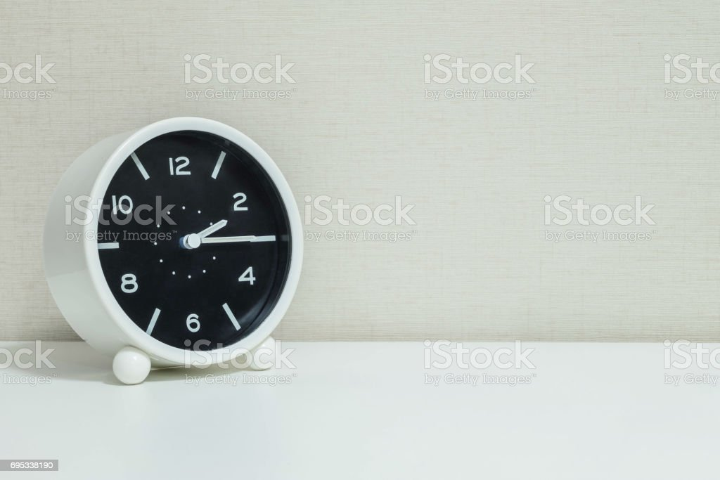 Closeup black and white alarm clock for decorate show a quarter past two o'clock or 2:15 p.m.on white wood desk and cream wallpaper textured background with copy space stock photo