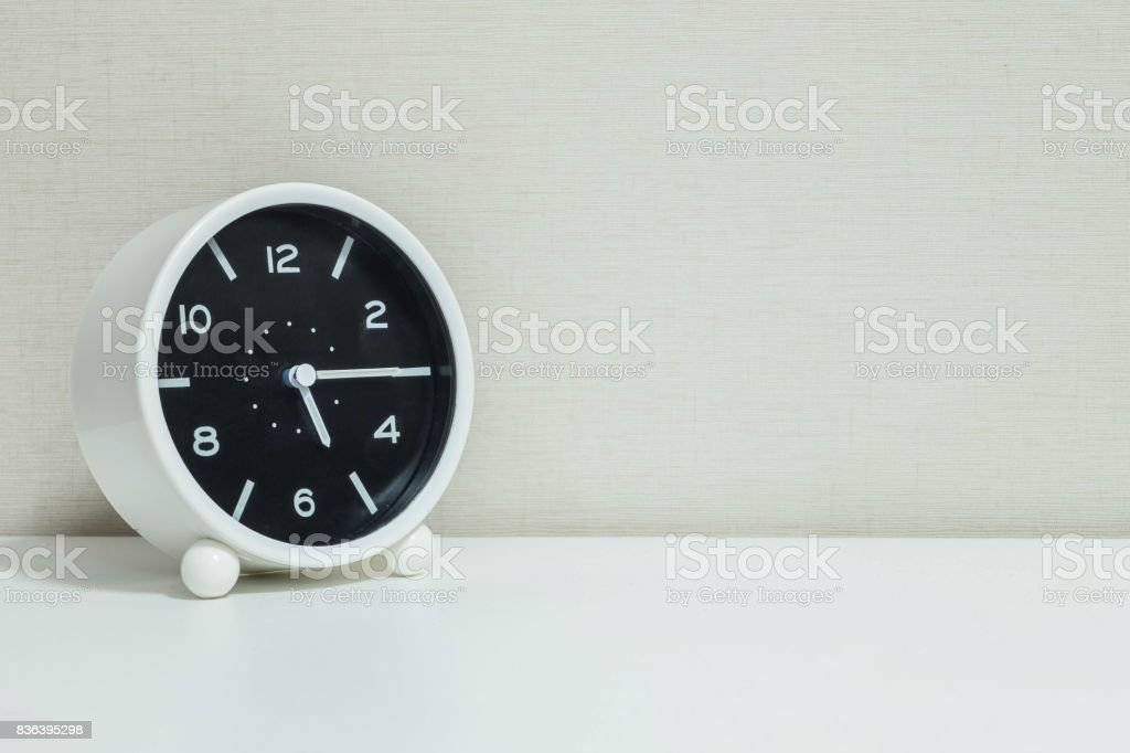 Closeup black and white alarm clock for decorate show a quarter past five o'clock or 5:15 p.m.on white wood desk and cream wallpaper textured background with copy space stock photo