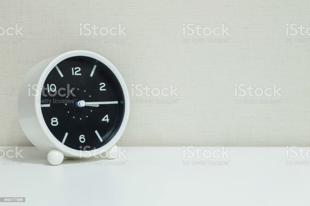 Closeup black and white alarm clock for decorate show a quarter past three o'clock or 3:15 p.m.on white wood desk and cream wallpaper textured background with copy space stock photo