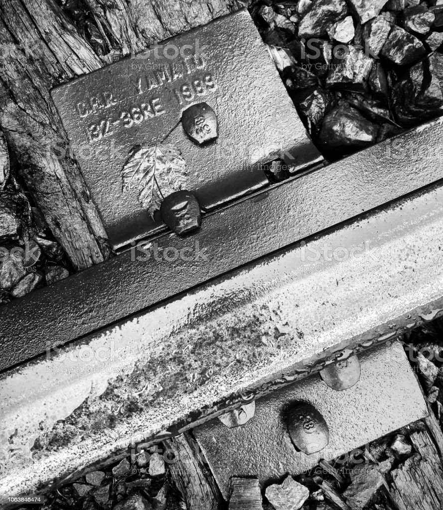 A close-up black and white image of a railroad baseplate and a track stock photo