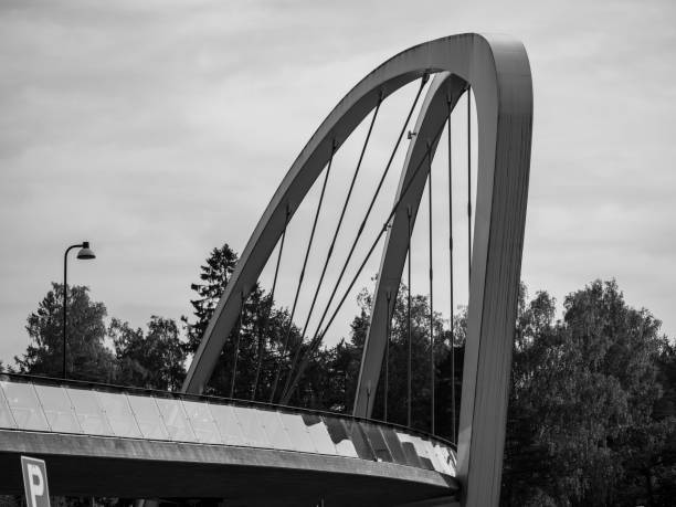 A close-up black and white shot of an arch walking bridge with reflecting glass railings. stock photo