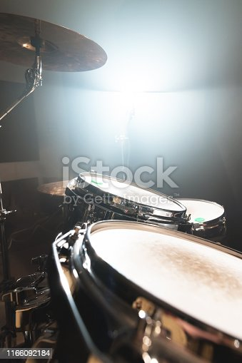 Close-up black drums A modern drum set prepared for playing in a dark rehearsal room on stage with a bright spotlight. The concept of percussion musical instruments.