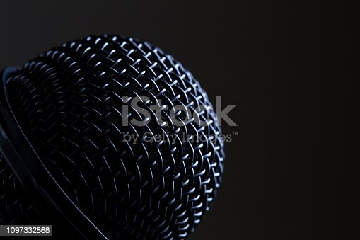 Close-up black microphone head isolated on black background.