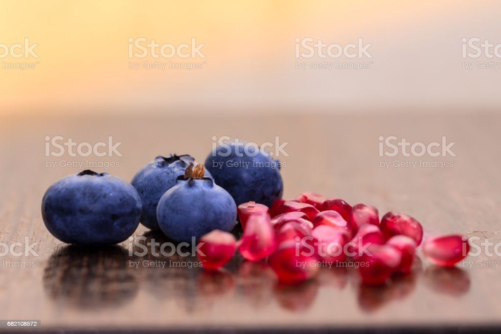 closeup blue berries Pomegranate seeds on wooden  table stock photo