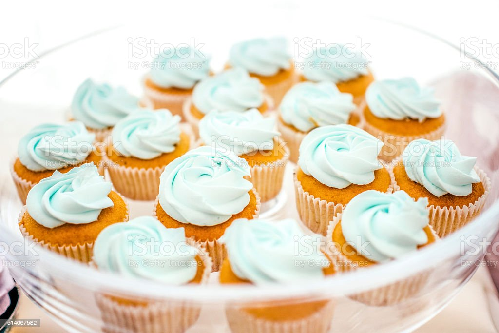 Close-up blue creme cupcakes on the glass plate stock photo