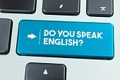 Close-Up Blue Laptop Keyboard With Do You Speak English Button. Horizontal composition with copy space. Technology and internet Concept.