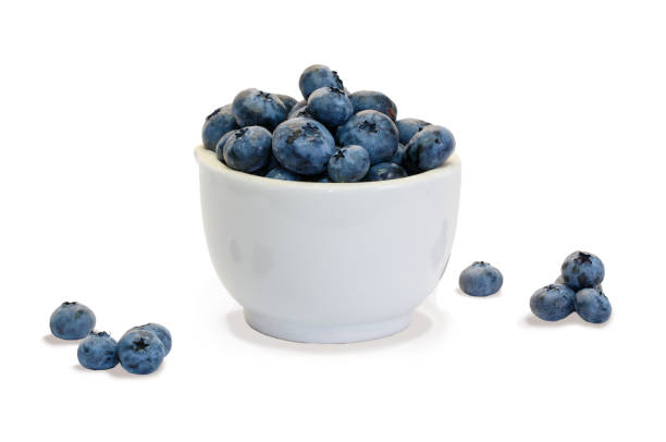 Closeup  blueberry in white ceramic cup  and small piles of blueberry on white background isolated stock photo