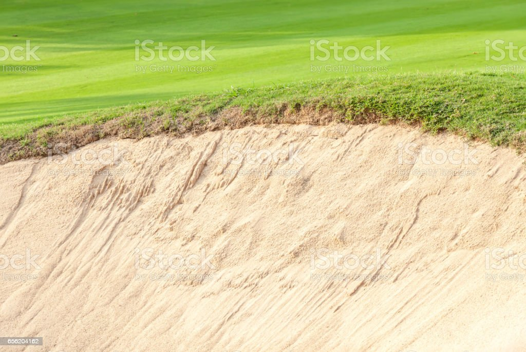 Close-up border of sand bunker contrasting on fresh grass in green golf course. stock photo
