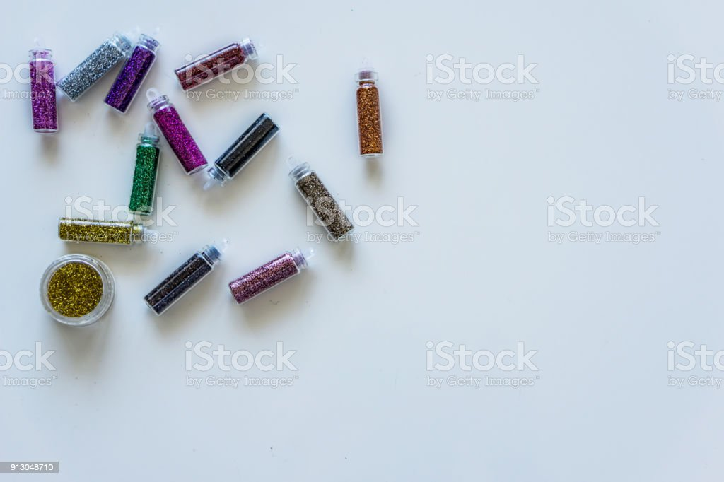 Close-up bottles of colorful glitter for makeup and manicure. Concept fashion and beauty. stock photo