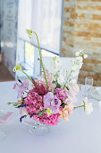 closeup bouquet set of fresh roses, astilbe, carnation, delphinium, eustoma, ornithogalum, lavender and hydrangea decorate table on wedding banquet. Event decoration with fresh flowers.