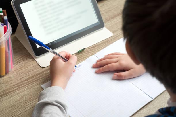 nahaufnahme junge lernen zu hause mit tablet und machen schulhausaufgaben. fernunterricht online-bildung oder zu hause bleiben konzept. weicher fokus. - homeschooling stock-fotos und bilder