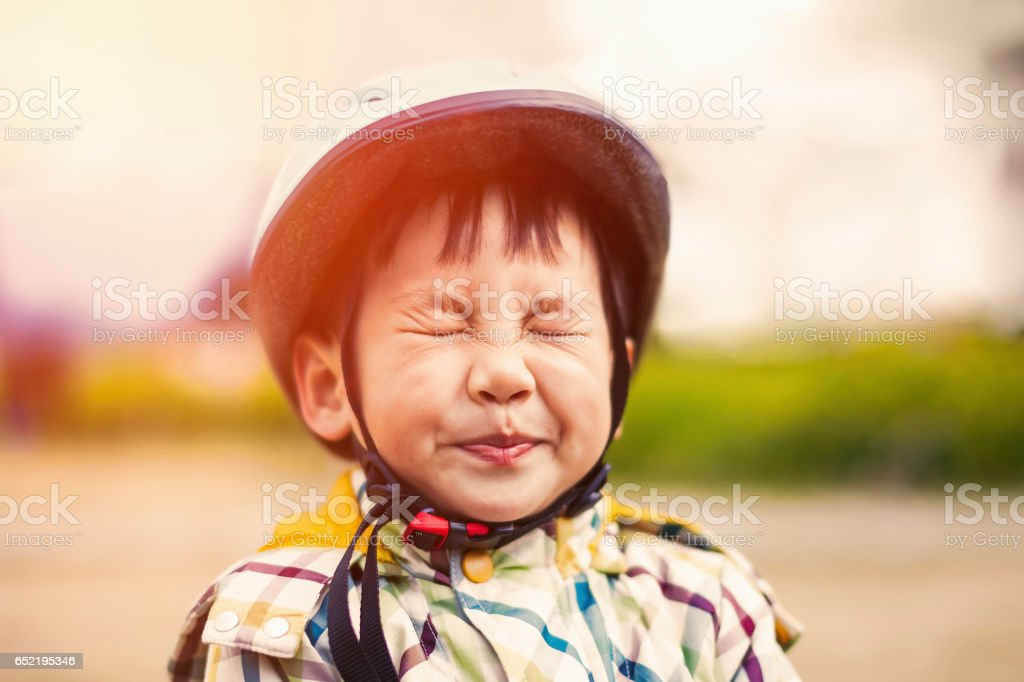 Close-up boy wearing a sports helmet, naughty eyes closed stock photo