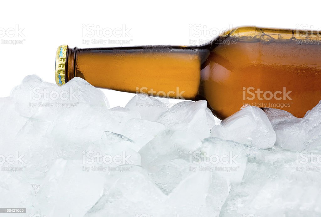 Close-up Brown bottle with Condensation cool in ice isolated royalty-free stock photo