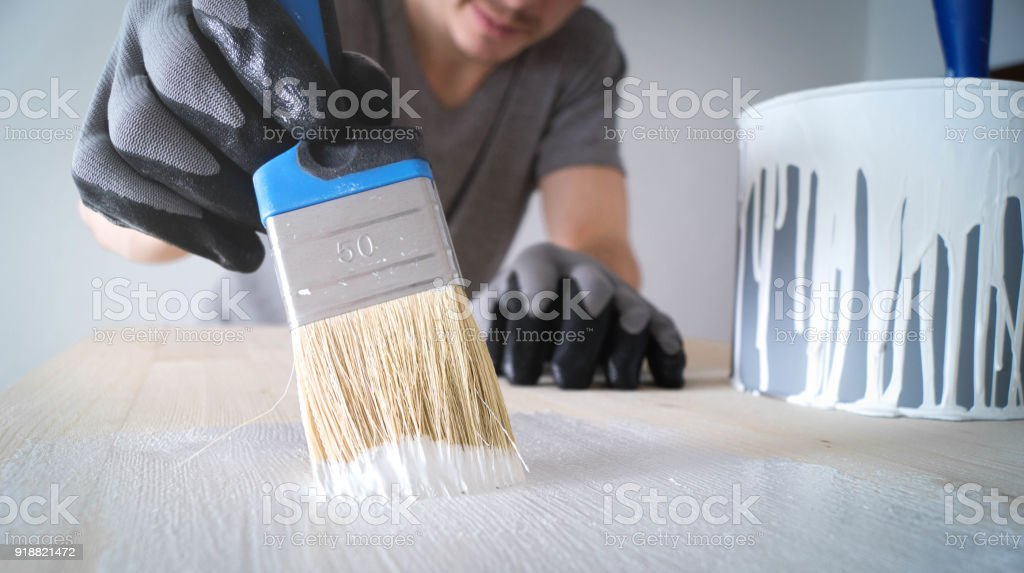 close-up: brush with white paint on a wooden table and a jar with paint stock photo