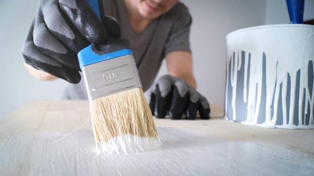 Nahaufnahme: Pinsel mit weißer Farbe auf einem Holztisch und ein Glas mit Farbe – Foto