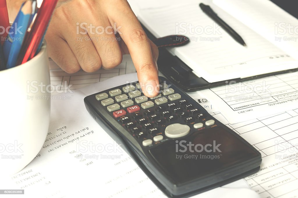 Close-up businessman's hand counting on calculator in office. stock photo